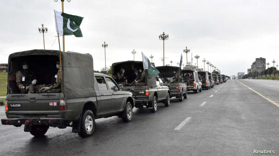 Pakistan's national flags flatter on an Army convey patrolling during a partial lockdown after Pakistan shut all markets,…