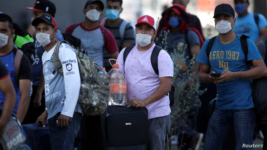 Migrants seeking for a U.S. work visa are pictured after being evicted from their hotel, which local authorities said was…