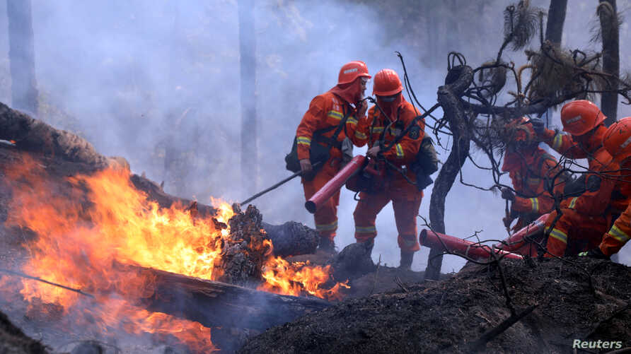 Firefighters work on extinguishing a forest fire that started near Xichang in Liangshan prefecture of Sichuan province, China…