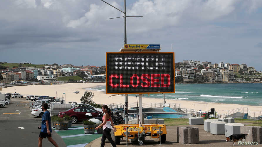 """People walk past a """"Beach Closed"""" sign at Bondi Beach, as the beach remains closed to prevent the spread of the coronavirus…"""