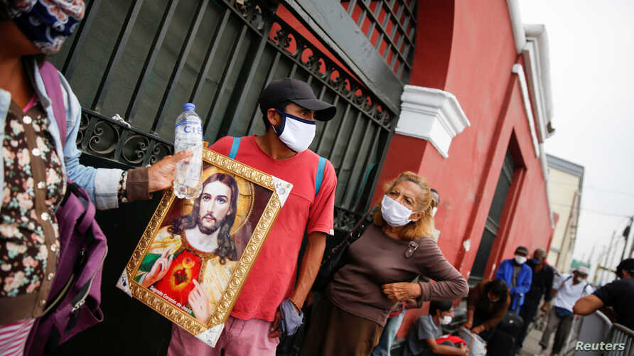 A homeless woman holding an illustration of Jesus waits outside the Plaza de Acho bullring, which the Peruvian government is…