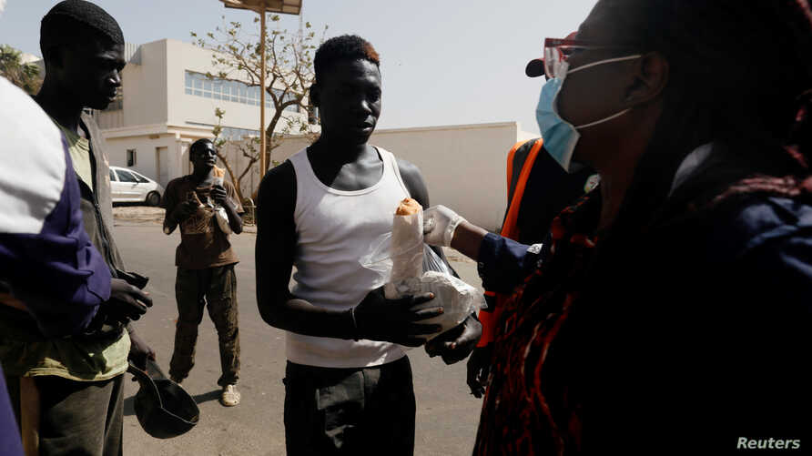 Faty, from the Village Pilote association wears a protective face mask during a food distribution to street children amid an…