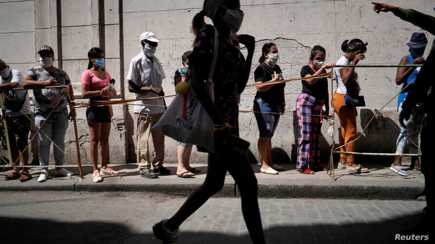 People wait in line to buy food amid concerns about the spread of the coronavirus disease (COVID-19), in downtown Havana, Cuba,…