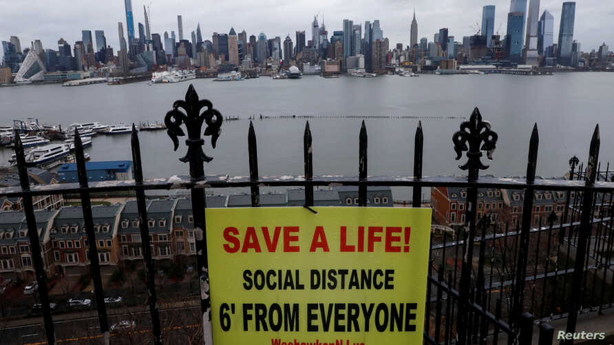 A sign promoting social distancing hangs from a fence in Hamilton Park above the Hudson River with the New York City skyline of…