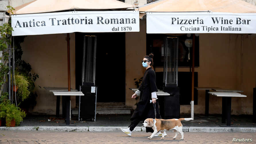 A woman wearing a protective mask walks her dog in Piazza Navona, as Italians remain under lockdown to prevent the spread of…