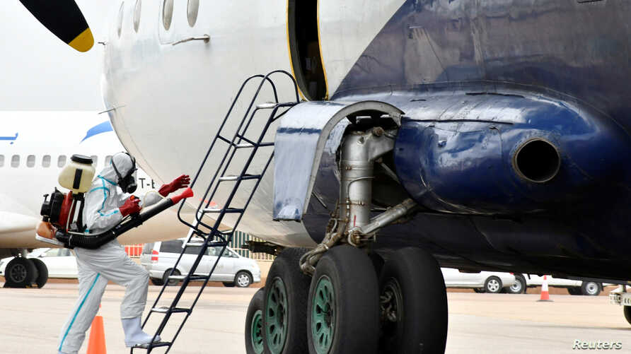 A member of a medical team wearing protective suit cleans the staircase to a plane at the airfield, to prevent the spread of…