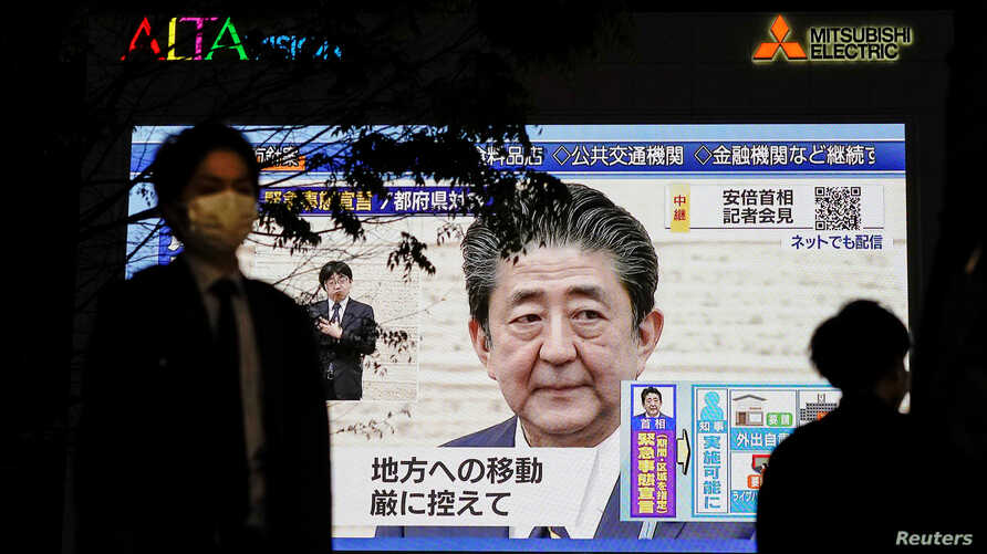 A pedestrian wearing a protective mask walks past a large screen on a building showing Japan's Prime Minister Shinzo Abe…