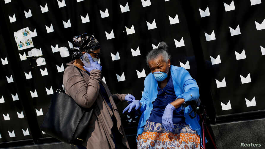 People seen along along 53rd Street wear personal protective equipment during the global outbreak of coronavirus disease (COVID…