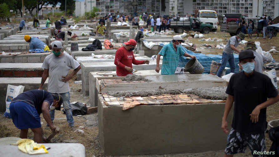 People construct burial vaults in the Angela Maria Canalis cemetery as the coronavirus disease (COVID-19) overwhelms sanitary…