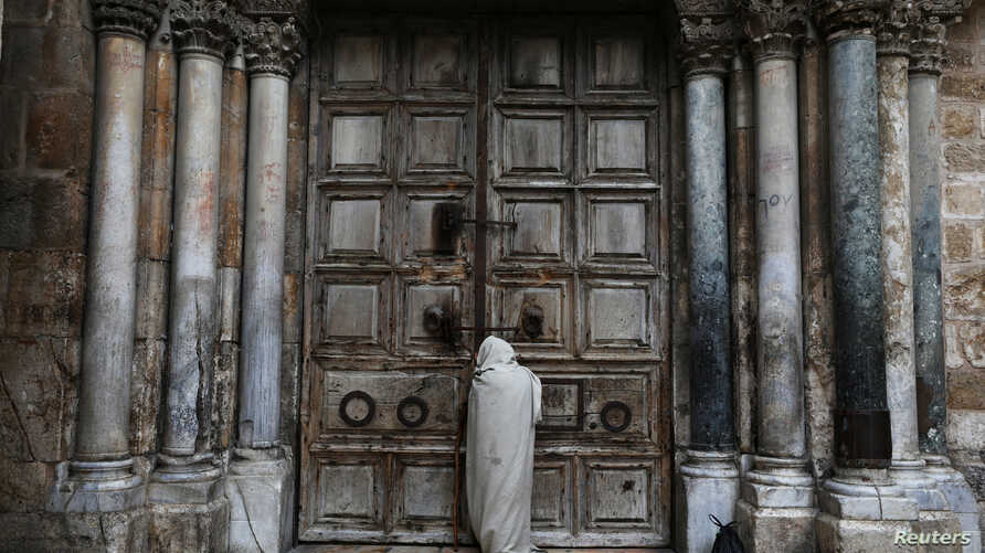 A man stands in front of the closed doors of the Church of the Holy Sepulchre on Good Friday amid the coronavirus disease …
