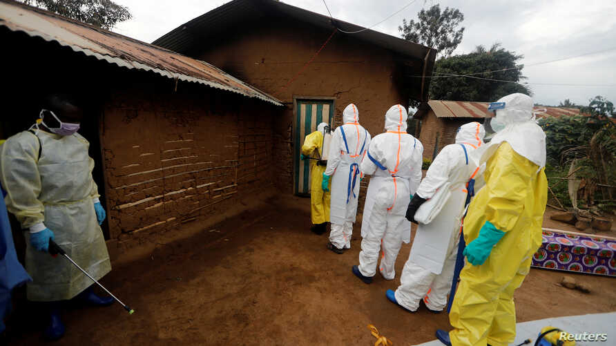 FILE PHOTO: Kavota Mugisha Robert (L), a healthcare worker who volunteered in the Ebola response, stands with decontamination…