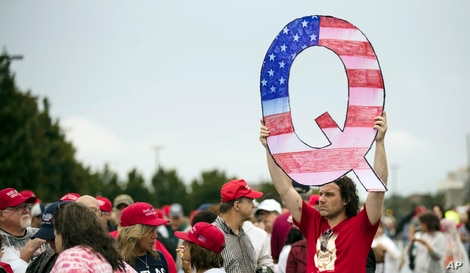 FILE - David Reinert holding a Q sign waits in line with others to enter a Trump campaign rally.