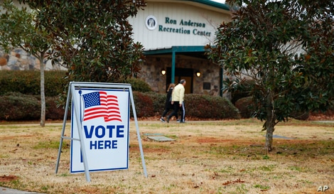 Voters return to their vehicles after early voting for the Senate runoff election, at Ron Anderson Recreation Center, Thursday,…