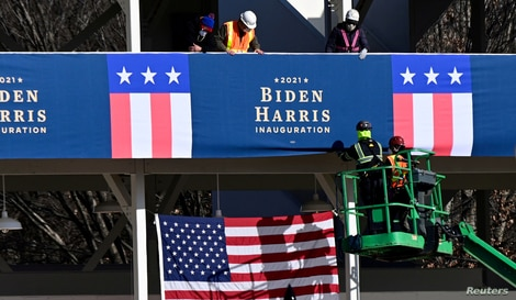 Workers place Biden-Harris inauguration banners on the inaugural parade viewing stand across from the White House.