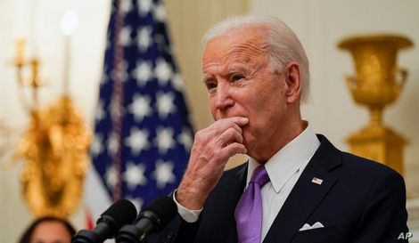 President Joe Biden pauses as he speaks about the coronavirus, accompanied by Vice President Kamala Harris