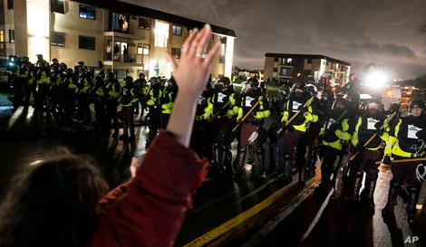 A demonstrator raises their hand while facing off against a perimeter of police as they defy an order to disperse during a…