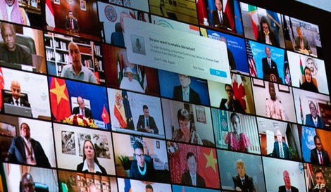 World leaders are shown on a screen as President Joe Biden speaks to the virtual Leaders Summit on Climate.