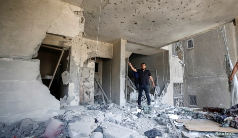 A Palestinian man gestures as he inspects a damaged building following an Israeli air strike, amid a flare-up.