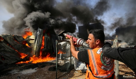 A Palestinian firefighter participates in efforts to put out a fire at a sponge factory.