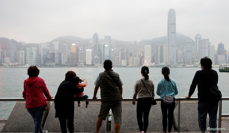 The Lai family, who are emigrating to Scotland, look out over the Hong Kong skyline on an outing to Tsim Sha Tsui