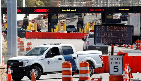 FILE PHOTO: A U.S. Customs and Protection vehicle stands beside a sign reading that the border is closed to non-essential…