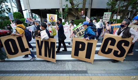 FILE - People opposing the Tokyo 2020 Olympics set to open in July amid the COVID pandemic, march near Tokyo's National Stadium, in Tokyo, Japan, May 9, 2021.