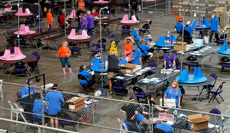 FILE - Maricopa county ballots cast in the 2020 election are examined and recounted by contractors working for Florida-based company Cyber Ninjas at Veterans Memorial Coliseum in Phoenix, Arizona, May 6, 2021.