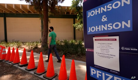 Carlos Arrendondo arrives for his appointment to get vaccinated, as banners advertise the availability of the Johnson & Johnson…