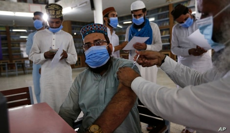 A student receives the Convidecia COVID-19 vaccine from a health worker at a vaccination center setup in Jamia Naeemia, an…