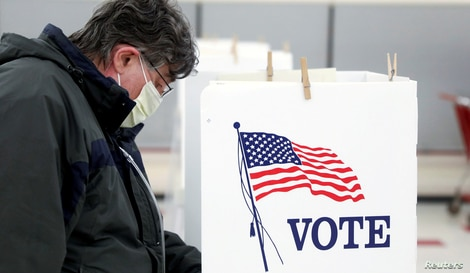 Voter Fred Hoffman fills out his ballot during the primary election in Ottawa, Illinois, U.S., March 17, 2020. The polling…
