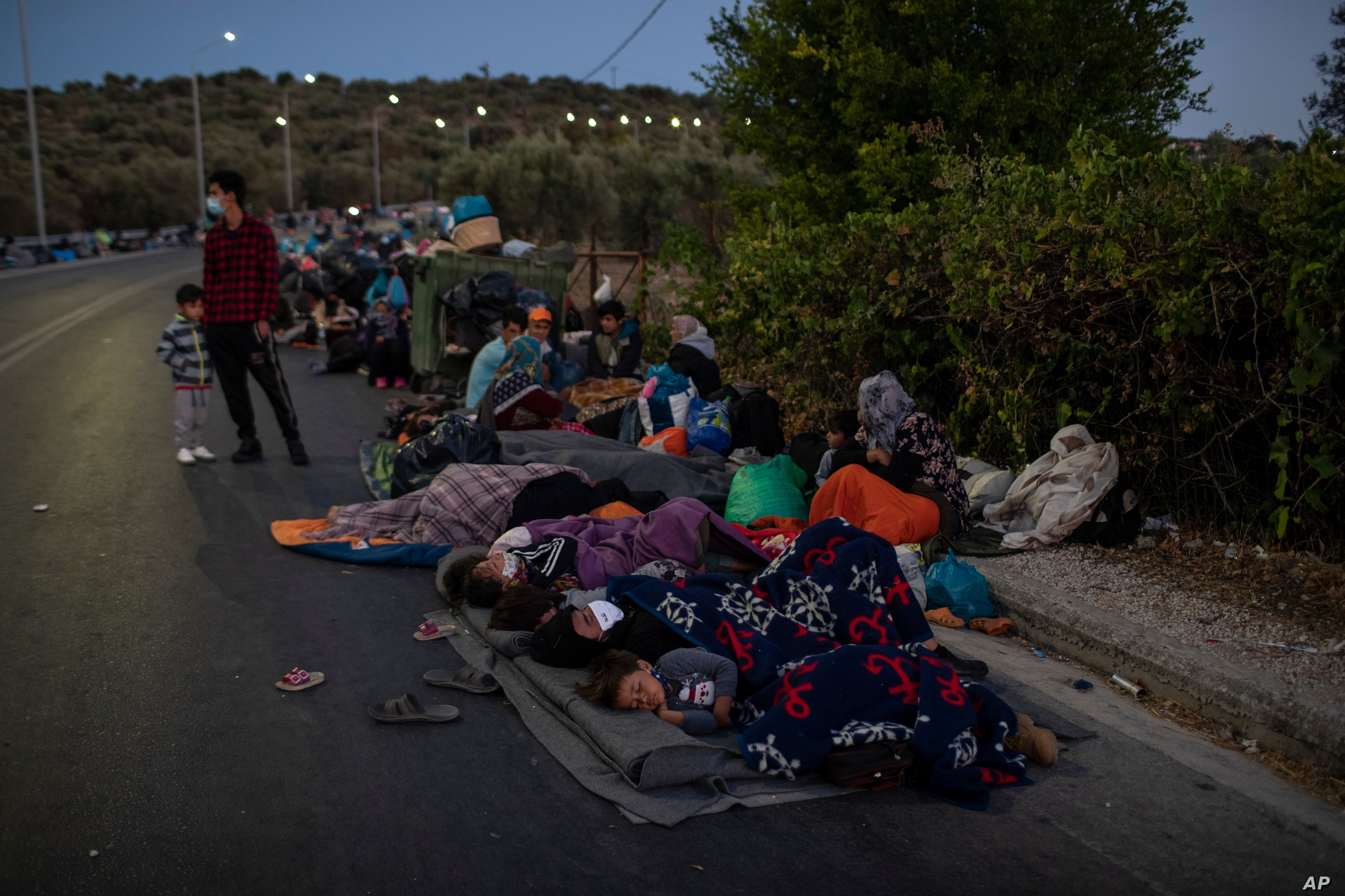 Migrants sleep on the road near the Moria refugee camp on the northeastern island of Lesbos Greece Thursday Sept. 10 2020