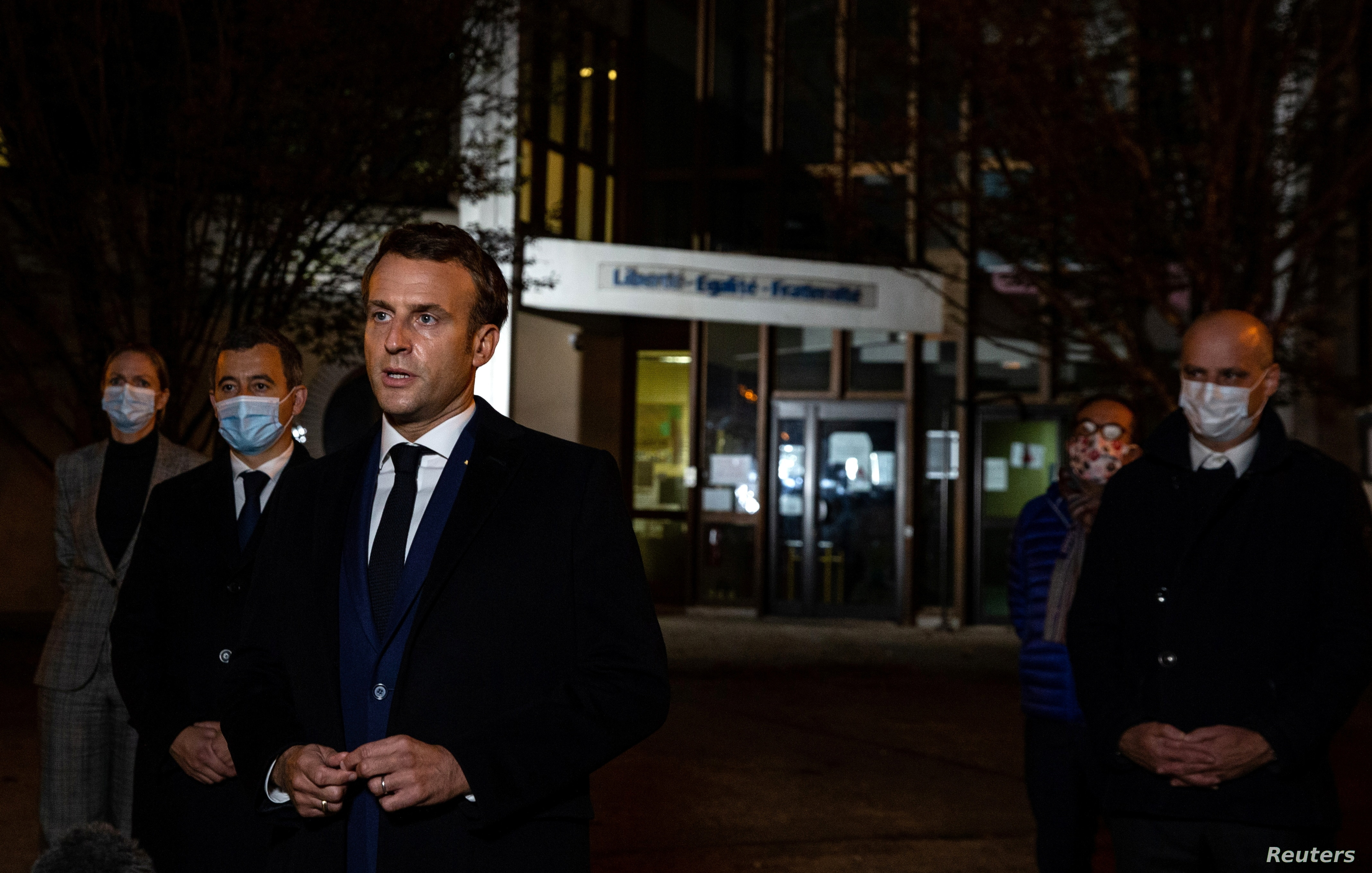 French President Emmanuel Macron flanked by offcials speaks to the press following a stabbing attack at a school in the Conflans-Sainte-Honorine suburb of Paris France Oct. 16 2020