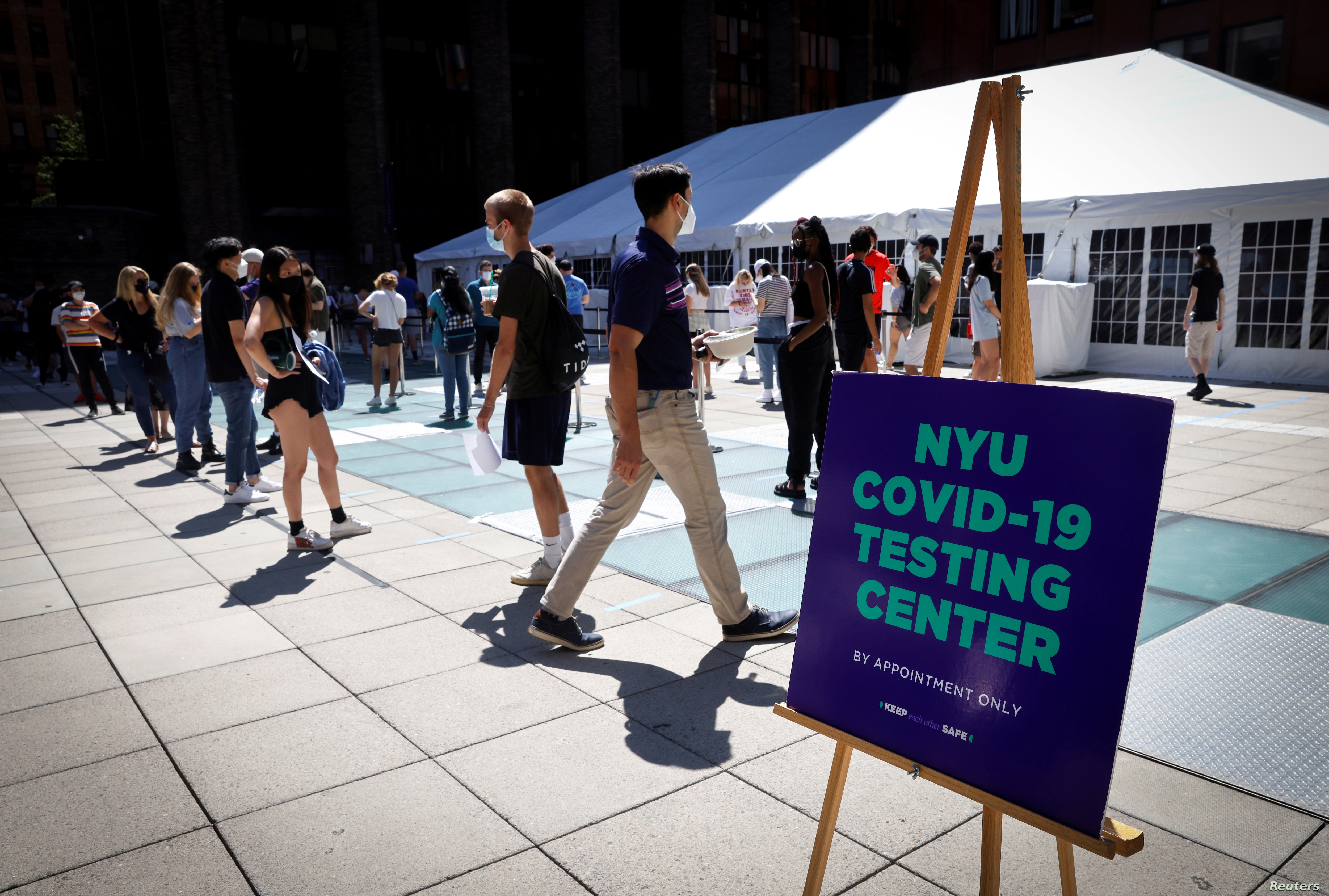 Students wait in line at a testing site for the COVID-19 set up for returning students faculty and staff on the main campus of New York University in Manhattan in New York City Aug. 18 2020