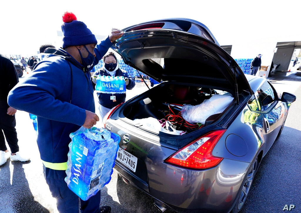 Water is loaded into the trunk of a car at a City of Houston water distribution site Friday Feb. 19 2021 in Houston. The