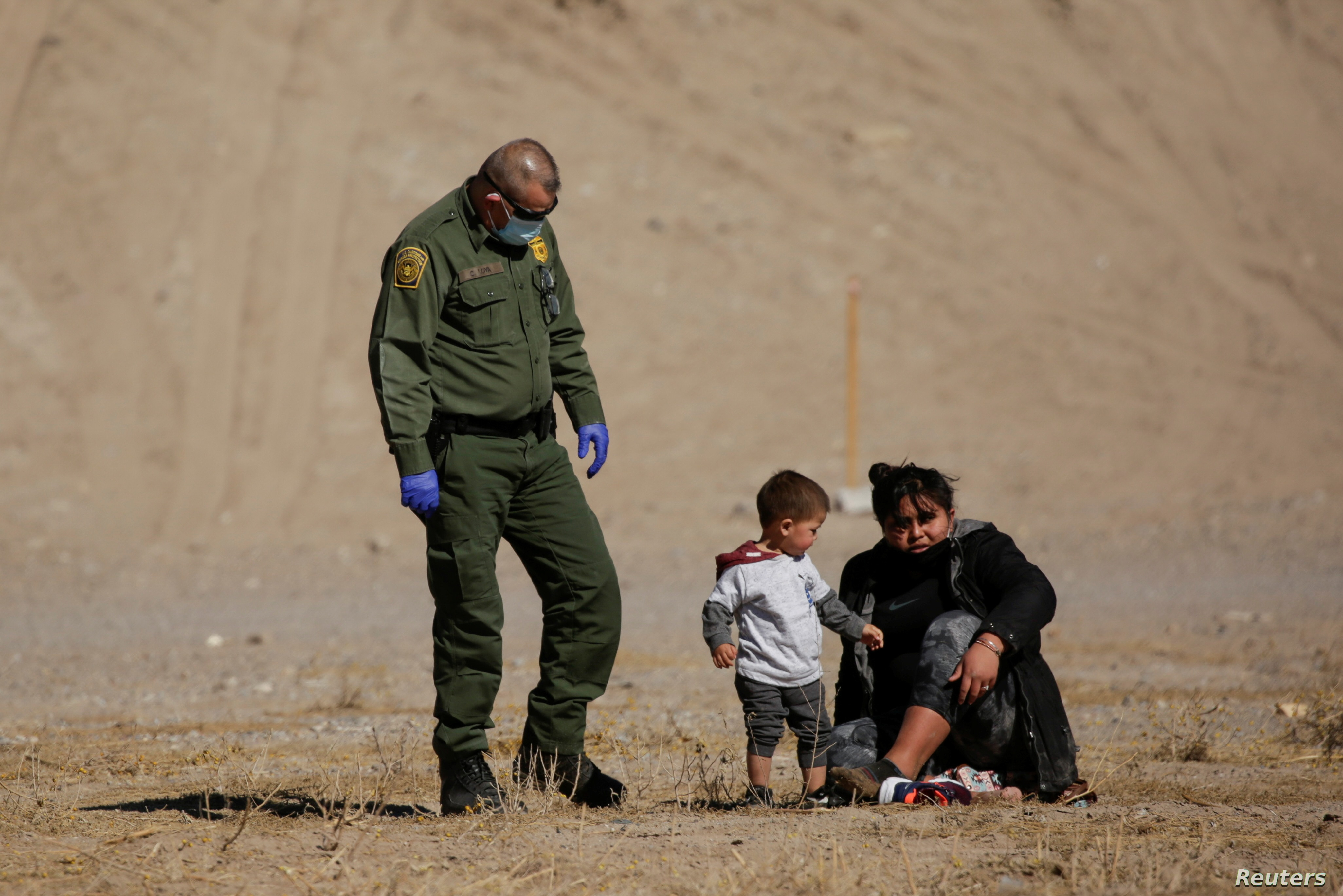 A migrant puts on her shoes after crossing the Rio Bravo river to turn herself in to a U.S. Border Patrol agent to request for