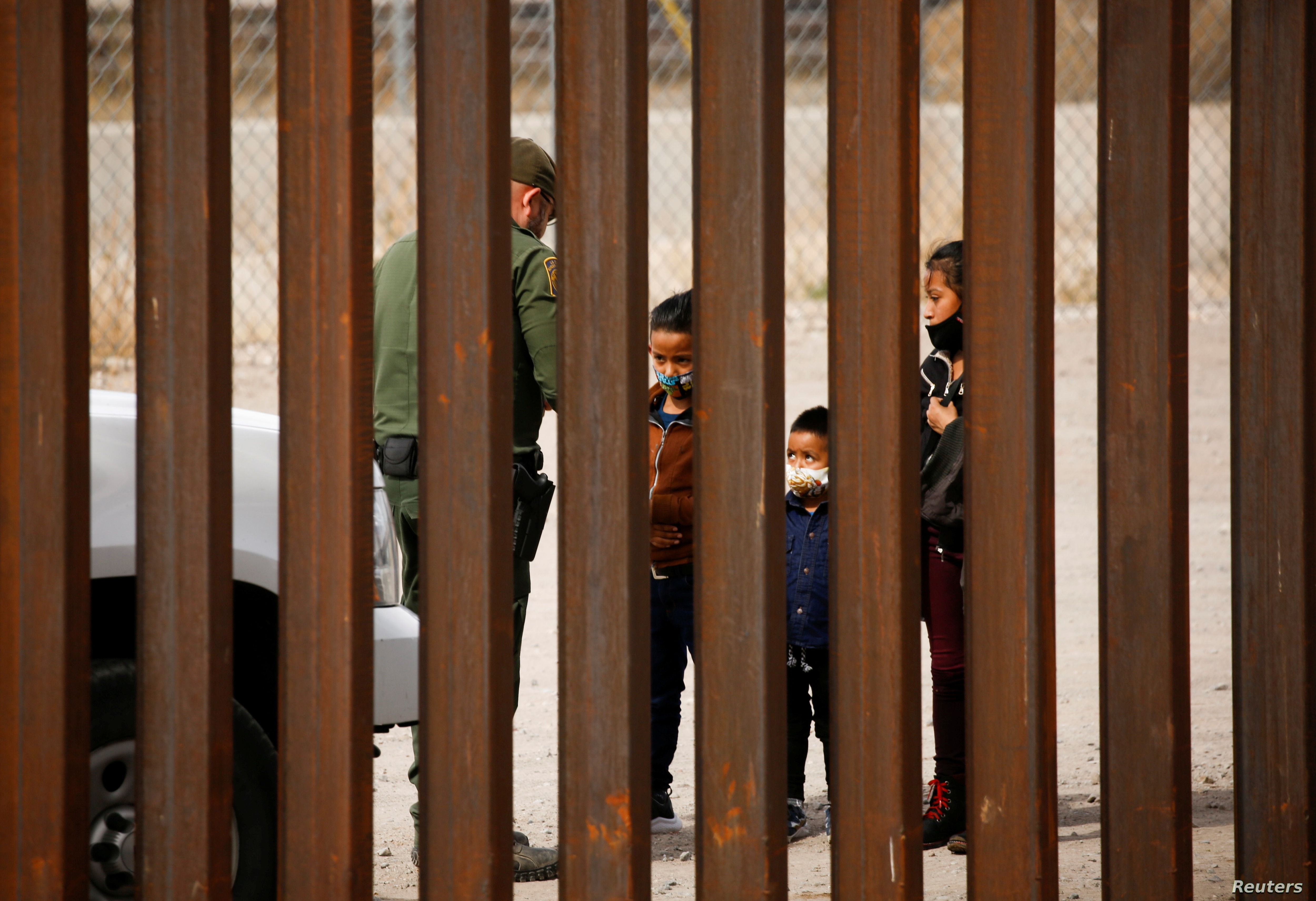 Migrants are detained by a U.S. Border Patrol agent after crossing the Rio Bravo river to turn themselves in to request for