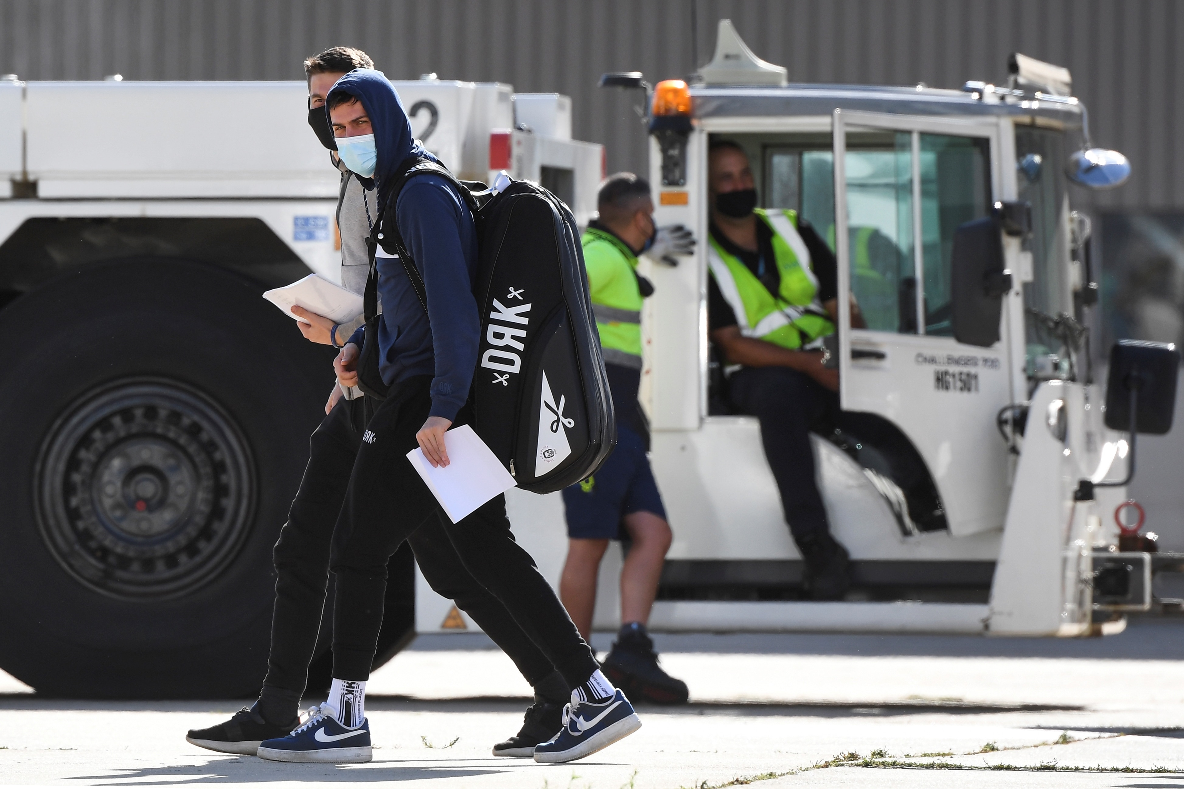 Tennis players and officials disembark from a flight after arriving in Melbourne