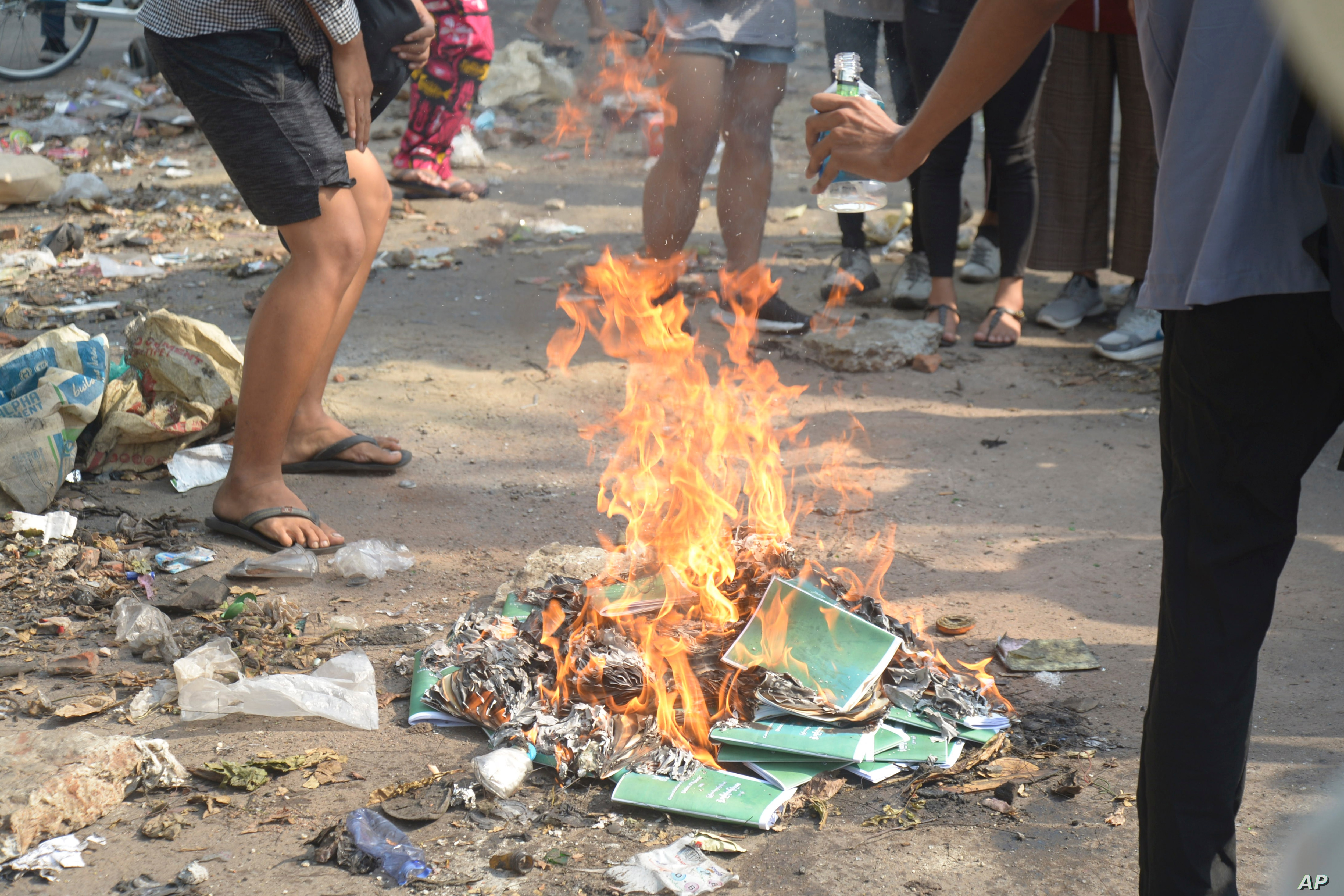 Anti-coup protesters burn constitution books at Tarmwe township in Yangon Myanmar Thursday