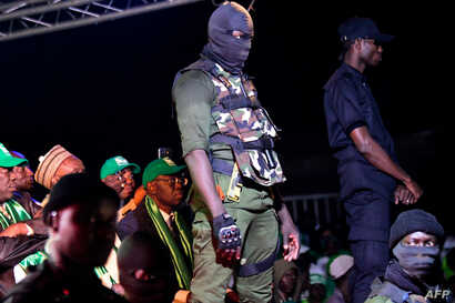 """FILE - Security agents stand guard during the campaign meeting of Issa Sall, presidential candidate and deputy president of the Senegalese """"Parti de l'Unite et du Rassemblement"""" (PUR), at the municipal stadium of Thiaroye, a suburb of Dakar, Feb. 3, ..."""