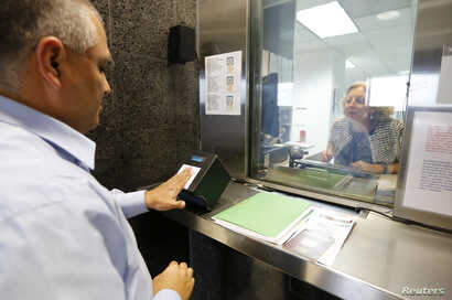 A man has his fingerprints electronically taken while taking part in a visa application demonstration