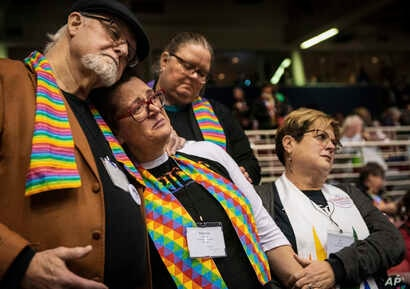 FILE - Ed Rowe, left, Rebecca Wilson, Robin Hager and Jill Zundel react to the defeat of a proposal that would allow LGBT clergy and same-sex marriage within the United Methodist Church at the denomination's 2019 Special Session of the General Confer...