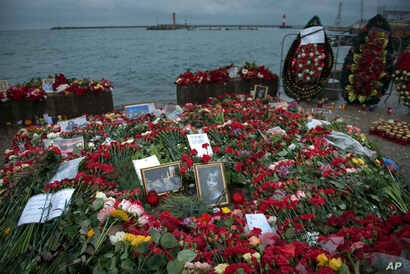 Flowers, candles and portraits are placed at a pier in honor of the victims of the military plane crash, in Sochi, Russia, Dec. 28, 2016.