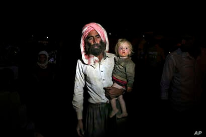 Displaced Iraqis from the Yazidi community cross the Syria-Iraq border in northern Iraq. A U.N. panel says the Islamic State is committing genocide, crimes against humanity and other war crimes against the Yazidi community in Iraq and Syria, Aug. 10,...