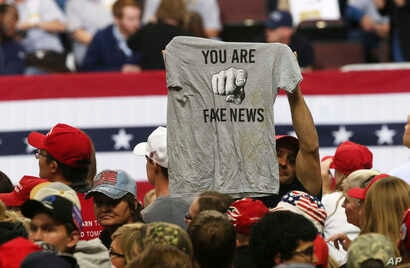 """FILE - In this Oct. 4, 2018 file photo, a Trump supporter holds up a T-shirt reading """"You Are Fake News"""" before a rally by President Donald Trump in Rochester, Minn. The Native American Journalists Association worries such rhetoric could impact free ..."""