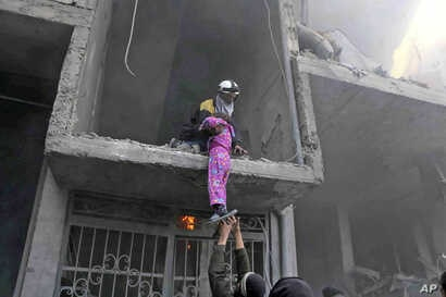 This photo released Feb. 21, 2018, provided by the Syrian Civil Defense group known as the White Helmets, shows a member of the Syrian Civil Defense group rescuing a young girl from a building damaged by airstrikes and shelling by Syrian government f...