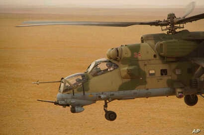 A Russian military helicopter flies over a desert in Deir el-Zour province, Syria, Sept. 15, 2017. A U.S.-backed force in Syria said a Russian airstrike wounded six of its fighters Saturday near Deir el-Zour city, while in southeast Syria, Syrian tro...