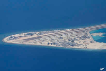 Chinese structures and an airstrip on the man-made Subi Reef at the Spratly group of islands in the South China Sea are seen from a Philippine Air Force C-130 transport plane of the Philippine Air Force, April 21, 2017.