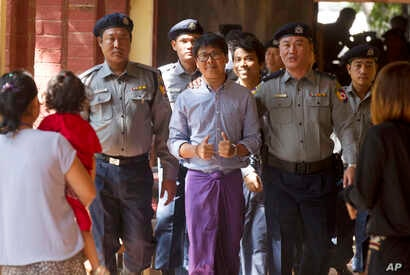 Reuters journalist Wa Lone, center, flashes thumps up as he is escorted by Myanmar police to court for trial, Feb. 1, 2018, on the outskirts of Yangon, Myanmar. The trial resumes for the two Reuters journalists charged of violating state secrets.