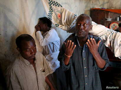 FILE - Family and friends weep and pray after preparing the body for burial of Ndayizeye Janvier Abdul, who they say was killed by members of the Imbonerakure, the youth wing of President Nkurunziza's ruling CNDD-FDD party in the district of Buterere...