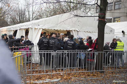 Migrants line up at the compound outside the Berlin Office of Health and Social Affairs (LAGESO) waiting to register in Berlin, Germany, Nov. 17, 2015.